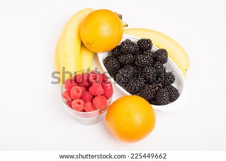 Fresh, whole fruit on a white background. Oranges Raspberries Blackberries and Bananas on White - stock photo