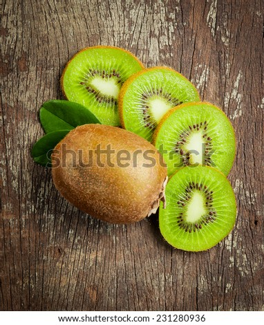Fresh Whole kiwi fruit and his sliced half on wooden background