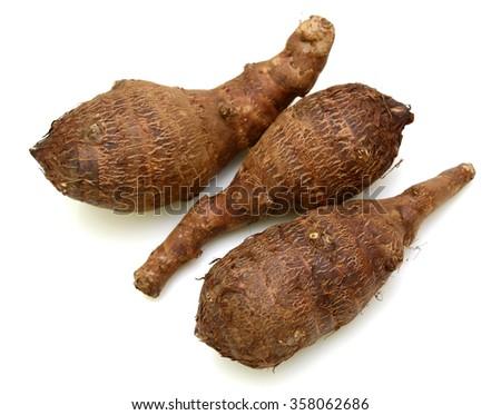Fresh whole taro roots over white background - stock photo