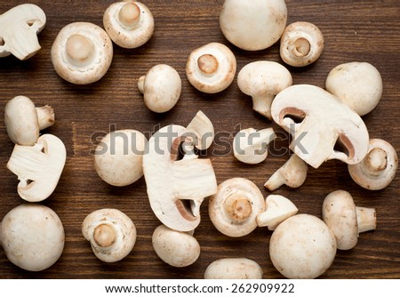 Fresh whole white button mushrooms, or agaricus, on a rustic wooden counter ready to be cleaned and washed for dinner top view  - stock photo