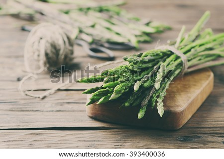Fresh wild asparagus on the wooden table, selective focus and toned image - stock photo