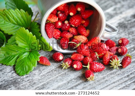 Fresh wild strawberries on an old wooden table - stock photo