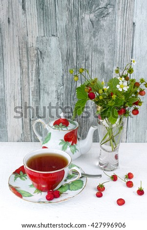 Fresh wild strawberry tea in an colorful cup and teapot and bouquet of ripe wild strawberries  in a vase on wooden background - stock photo