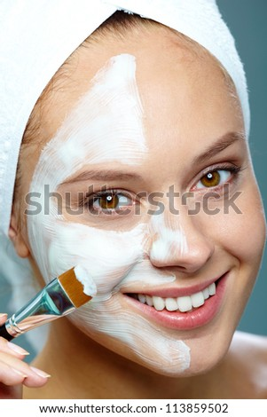 Fresh woman applying facial mask onto her face with brush