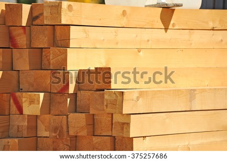 Fresh wooden beam, stacked at construction site - stock photo