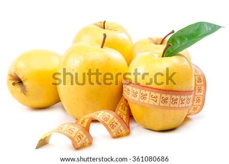 Fresh yellow apples and measuring tape isolated on a white background. - stock photo