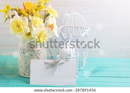Fresh  yellow daffodils flowers,  candles in decorative bird cages and  empty tag  in ray of light on turquoise  painted wooden planks against white wall. Selective focus. Place for text.  - stock photo