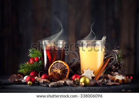 fresh yellow eggnog and fruity red mulled wine with Christmas decoration - stock photo