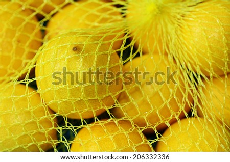 Fresh yellow lemons in plastic netting In Market. Food background texture - stock photo