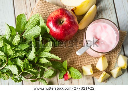 fresh yogurt in a glass with granola with  fresh apple - stock photo