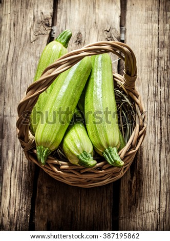 Fresh zucchini in the basket. On wooden background. - stock photo