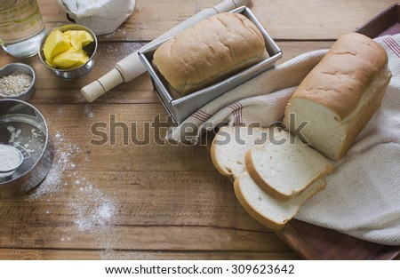 Freshly baked and sliced plain sandwich bread loaf on rustic wooden table top. Baking process. Over head view. - stock photo