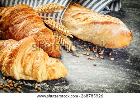 Freshly baked baguette and croissants in rustic setting with copyspace