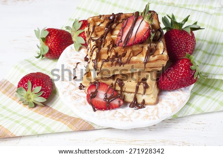 Freshly baked belgium waffles with chocolate sauce and strawberries on wooden table, selective focus - stock photo
