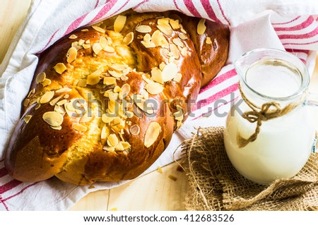 Freshly baked braided bread with almonds and milk  on rustic table - stock photo