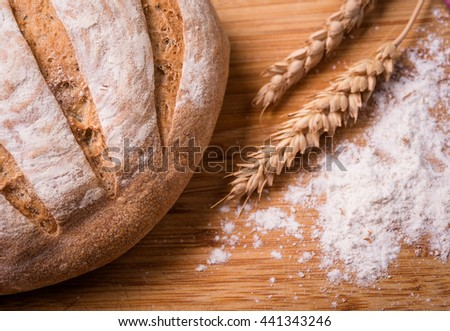 Freshly baked bread in rustic setting on wooden background - stock photo