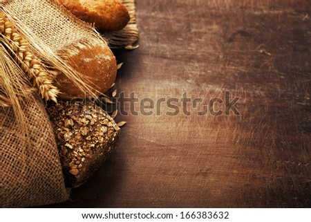 Freshly baked  bread on wooden table - stock photo