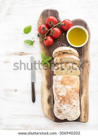 Freshly baked ciabatta bread with cherry-tomatoes, olive oil, basil and salt on walnut wood board over white background, top view, copy space - stock photo