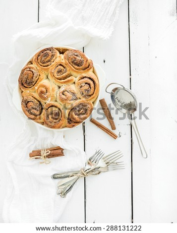 Freshly baked cinnamon buns in a dish on a rustic white wooden table, top view - stock photo