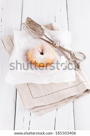 Freshly baked cinnamon sugared doughnuts on baking paper and linen napkin with silver vintage cake tongs on white wooden background. Elegant rustic still life - stock photo