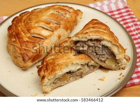 Freshly baked Cornish pasties on a plate - stock photo