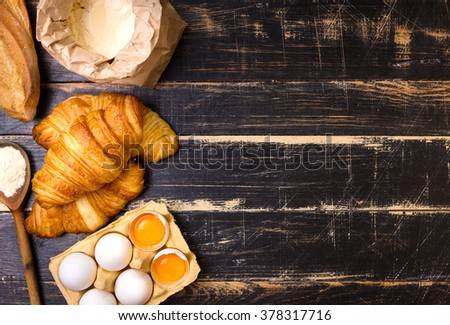 Freshly baked croissants and baguette with flour, wooden spoon, eggs and egg yolks in a carton tray on the dark wooden background. Baking/pastry background. Free space for text - stock photo