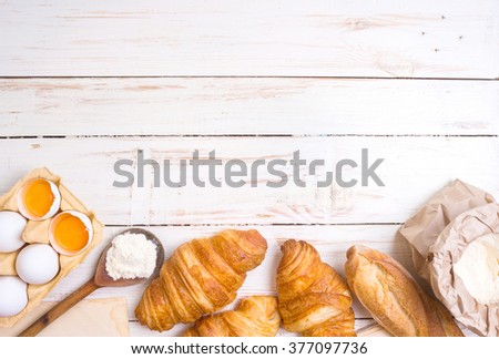 Freshly baked croissants and baguette with flour, wooden spoon, piece of paper, eggs and egg yolks in a carton tray on the white wooden table. Baking/pastry background. Free space for text - stock photo
