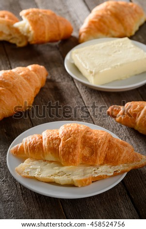 Freshly baked croissants for snack. French specialty on white plate and on the dark wooden table. Special plate for butter. Rural interior.