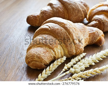 Freshly baked croissants on rustic background with copyspace.