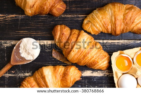 Freshly baked croissants with flour, rolling pin, spoon, eggs and egg yolks in a carton tray on the dark wooden background. Ingredients for baking. Top view - stock photo