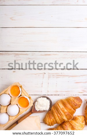 Freshly baked croissants with flour, wooden spoon, piece of paper, eggs and egg yolks in a carton tray on the white wooden table. Baking/pastry background. Free space for text - stock photo