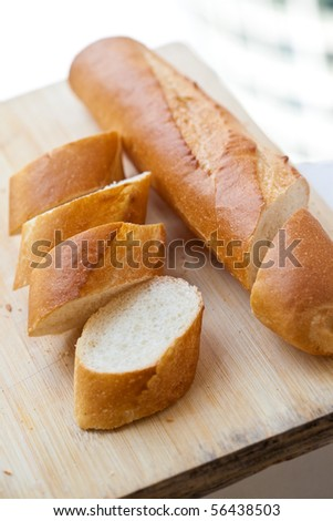 Freshly baked french baguette on wooden board - stock photo
