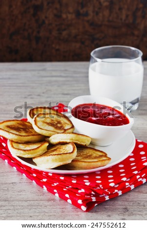 freshly baked fritters on a plate, strawberry jam and milk on the table. traditional european cuisine. selective focus - stock photo