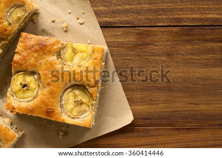 Freshly baked homemade banana and cinnamon cake pieces, photographed overhead with natural light (Selective Focus, Focus on the top of the cake pieces) - stock photo