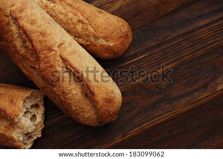Freshly baked homemade bread on rustic dark wood background.  Low key still life with directional natural lighting and copy space. - stock photo