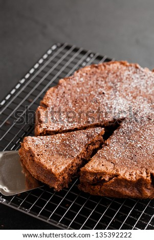 Freshly baked homemade chocolate cake on metal cooling rack with cut slice and cake server utensil on dark background - stock photo