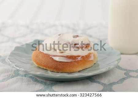 Freshly baked homemade cinnamon roll with cream cheese buttercream frosting and an antique bottle of milk on a blue and white place mat - stock photo