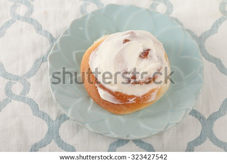 Freshly baked homemade cinnamon roll with cream cheese buttercream frosting on a blue and white place mat - stock photo