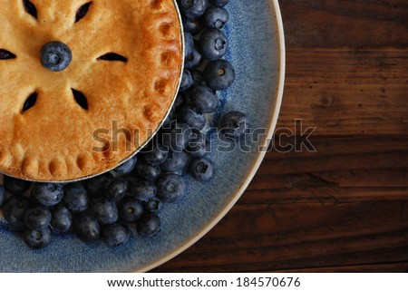 Freshly baked (individual sized) blueberry pie on vintage plate with fresh berries.  Rustic wooden table as background.  Closeup from above with natural directional lighting.