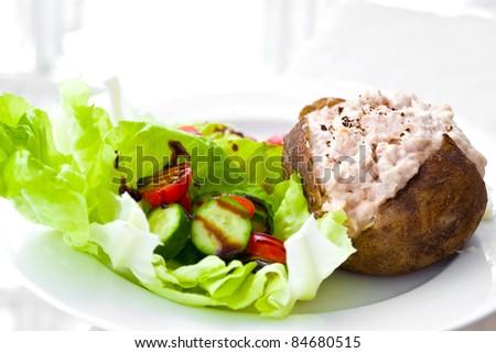 Freshly baked jacket potato with tuna mayonnaise and salad - stock photo