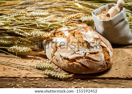 Freshly baked loaf of bread and a bag with grains