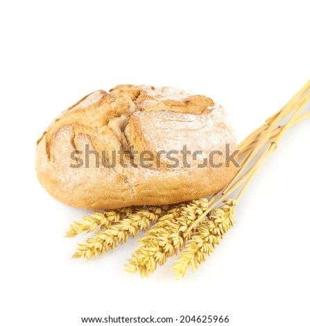 Freshly baked loaf of bread next to a pile of the ears of wheats, composition isolated over the white background