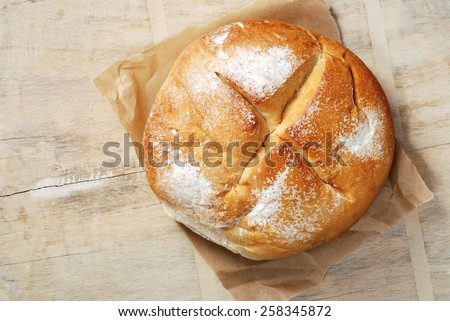 Freshly baked mountain bread on crumpled parchment paper over rustic wood cutting board. - stock photo