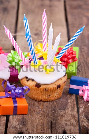 Freshly baked muffins on wooden table,  Homemade birthday cupcake iced with candles and birthday presents