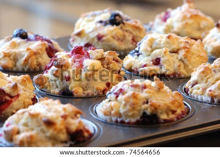 Freshly baked muffins with mixed berries and white chocolate - stock photo
