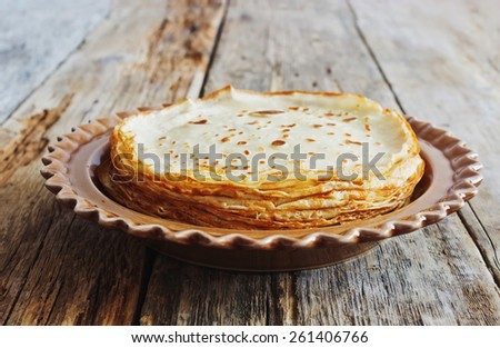 freshly baked pancakes in a ceramic plate on old wooden background. homemade pastries. shrovetide - stock photo