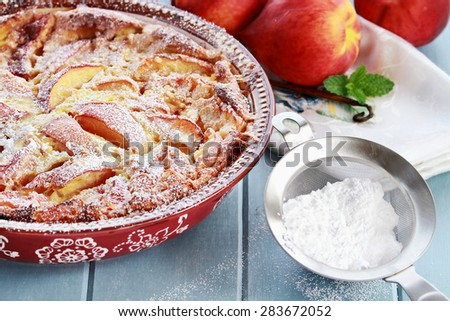 Freshly baked Peach Clafouti with powered sugar. Extreme shallow depth of field with selective center of dish.  - stock photo