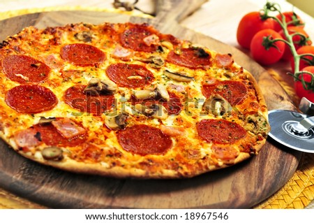 Freshly baked pepperoni pizza on wooden board - stock photo