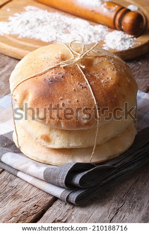 freshly baked pita bread on a wooden table close up on a background of a rolling pin and flour  - stock photo