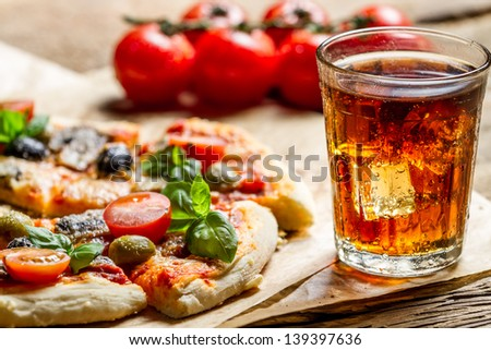 Freshly baked pizza and served with cold drink - stock photo